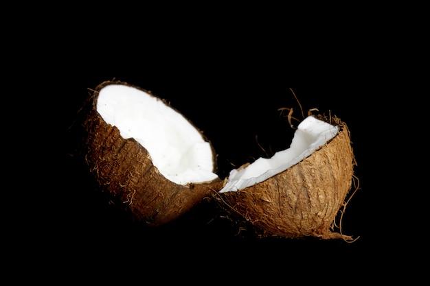 Rijpe kokosnoot is verdeeld in twee helften geïsoleerd op een zwarte