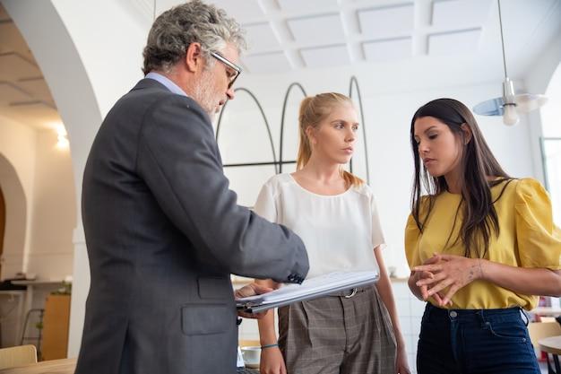 Rijpe kredietinspecteur die met kladblok jonge ondernemers ter plaatse bezoekt