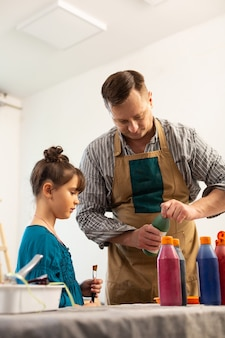 Rijpe kunstleraar die bruine schort draagt die verf voor meisje opent