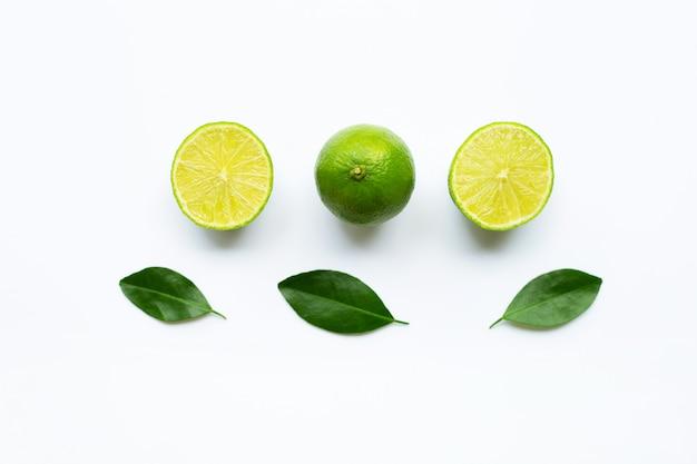 Rijpe limoenen met groene bladeren op wit.