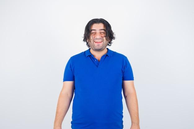 Rijpe man die rechtop staat, grimassen in blauw t-shirt, spijkerbroek en op zoek vrolijk, vooraanzicht.