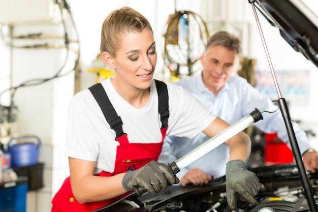 Rijpe man en vrouwelijke automonteur in workshop