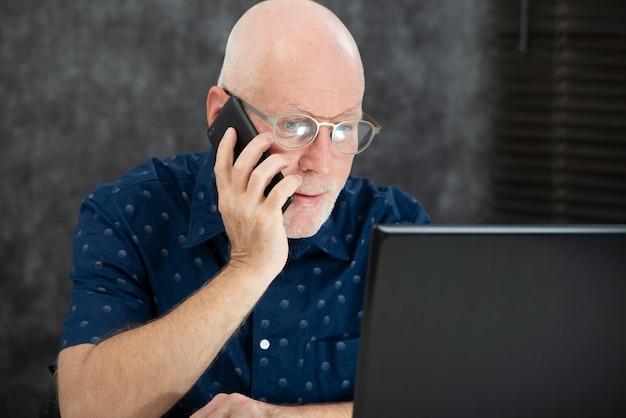 Rijpe man met een baard en een blauw shirt op kantoor