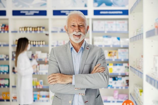 Rijpe man met gekruiste armen staat in een apotheek