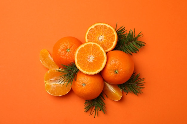 Rijpe mandarijnen en pijnboomtakken op sinaasappel