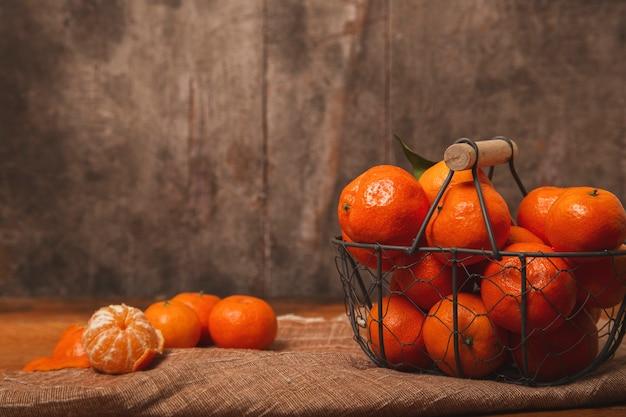 Rijpe mandarijnen in een oude metalen mand op een houten tafel.