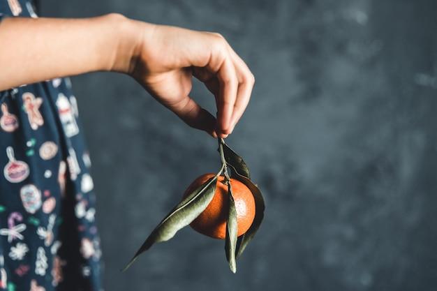Rijpe mandarijnen. kinderen houden mandarijnen vast met groene bladeren die net uit een boom zijn geplukt