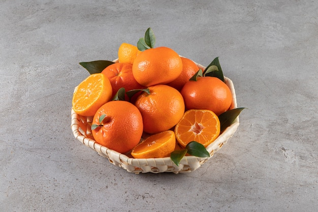 Rijpe mandarijnen met bladeren die in rieten mand op steen worden geplaatst