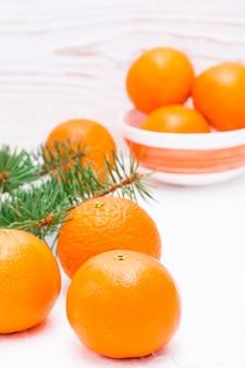 Rijpe mandarijnen op een tafel en in een kom en dennentakken