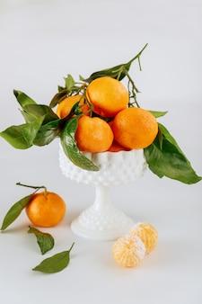Rijpe mandarijnen van florida met groene bladeren in witte kom