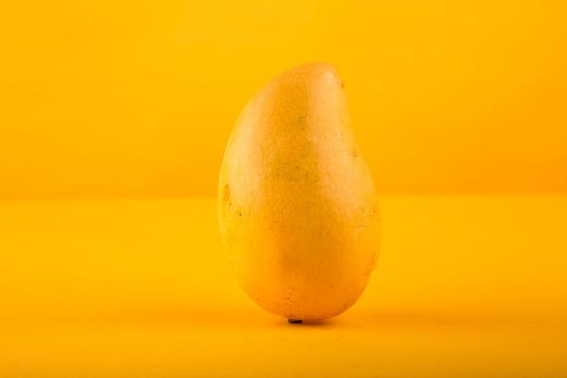 Rijpe mango die op gele achtergrond wordt geïsoleerd