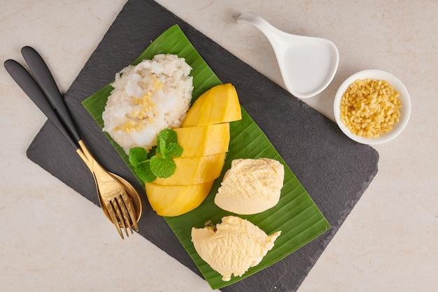 Rijpe mango en kleefrijst, ijs met kokosmelk op stenen oppervlak, thais zoet dessert op zomerseizoen. tropisch fruit. dessert fruit. bovenaanzicht.