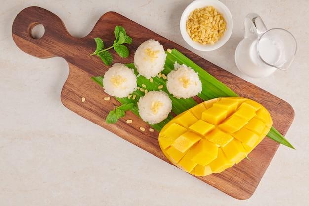 Rijpe mango en kleefrijst met kokosmelk op houten plaat op stenen oppervlak, tropisch fruit. dessert fruit. thais zoet dessert op zomerseizoen.