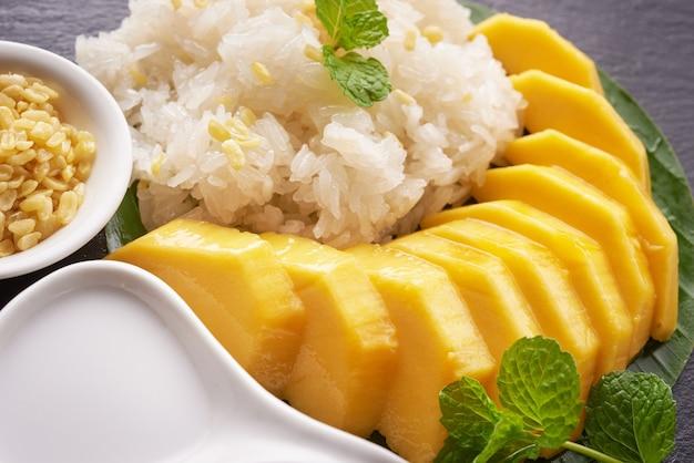 Rijpe mango en kleefrijst met kokosmelk op stenen oppervlak, thais zoet dessert op zomerseizoen.