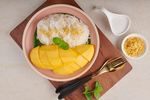 Rijpe mango en plakkerige rijst met kokosmelk in een plaat op steenoppervlakte, thais zoet dessert op zomerseizoen.