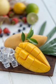 Rijpe mango op een houten plaat met ijsblokjes en fruit als achtergrond