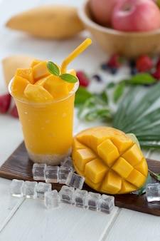 Rijpe mango smoothies op een houten plaat met ijsblokjes en fruit als achtergrond