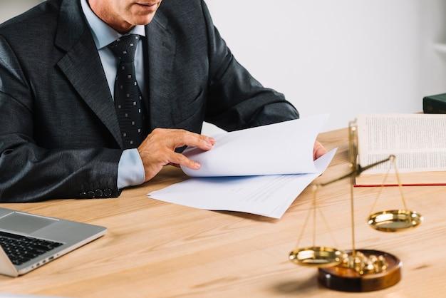Rijpe mannelijke advocaat die de documentpagina's op het bureau draait
