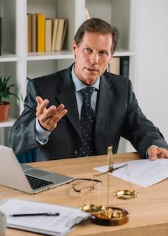 Rijpe mannelijke advocaatzitting in de rechtszaal die advies geeft