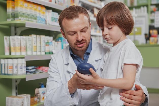 Rijpe mannelijke apotheker die weinig jongen helpt bij drogisterij