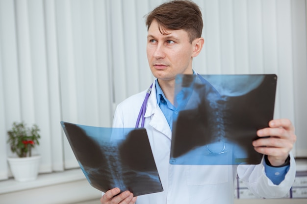 Rijpe mannelijke arts die bedachtzaam weg kijkt terwijl het onderzoeken van de röntgenscans van de nek van de patiënt