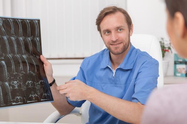 Rijpe mannelijke arts die mri-scan van een patiënt onderzoekt