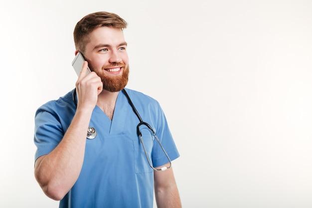 Rijpe mannelijke arts die op mobiele telefoon met glimlach spreekt terwijl status tegen witte muur