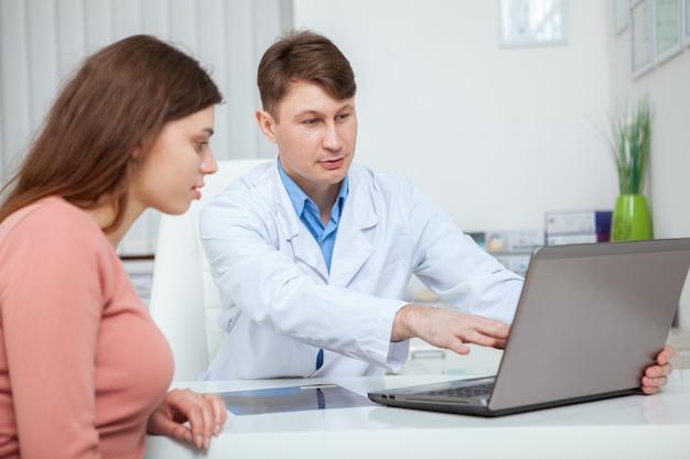 Rijpe mannelijke arts die tijdens medisch overleg iets op laptopscherm toont aan zijn vrouwelijke patiënt
