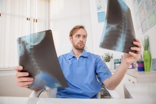 Rijpe mannelijke arts die x-ray scan van een patiënt onderzoekt
