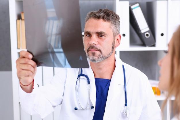 Rijpe mannelijke arts houdt in wapen en bekijkt xray fotografie