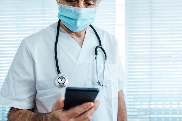 Rijpe mannelijke arts - verpleegster die gezichtsmasker draagt, die mobiele telefoon bekijkt naast een het ziekenhuisvenster. covid-19 en medicijnconcept