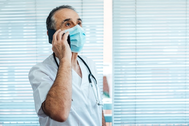 Rijpe mannelijke arts - verpleegster die gezichtsmasker draagt, die op mobiele telefoon naast een het ziekenhuisvenster spreekt. covid-19 en medicijnconcept