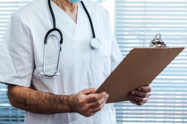 Rijpe mannelijke arts - verpleegster die gezichtsmasker draagt, op mobiele telefoon spreekt en een rapport naast een het ziekenhuisvenster houdt. covid-19 en medicijnconcept