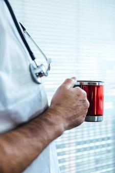Rijpe mannelijke arts - verpleegster die koffie in een het ziekenhuisvenster heeft. covid-19 en medicijnconcept
