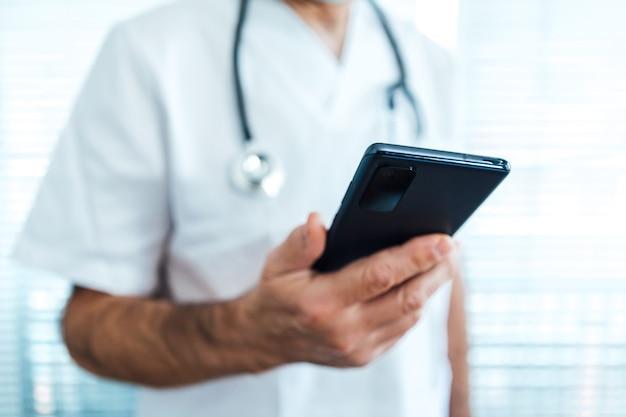 Rijpe mannelijke arts - verpleegster, die mobiele telefoon bekijkt naast een het ziekenhuisvenster. covid-19 en medicijnconcept