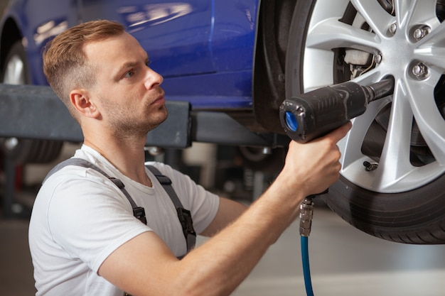 Rijpe mannelijke automonteur die bij de garage werkt