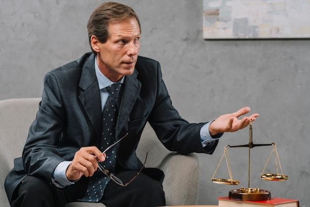 Rijpe mannelijke wettelijke adviseur die gesprek in het bureau hebben