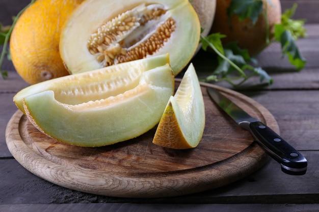 Rijpe meloenen met groene bladeren op houten tafel close-up