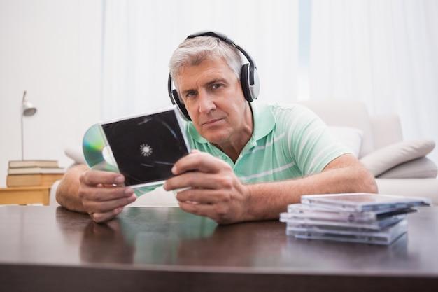 Rijpe mens die aan cd's luistert