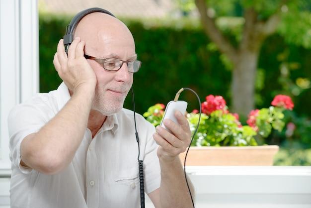 Rijpe mens die aan muziek luistert