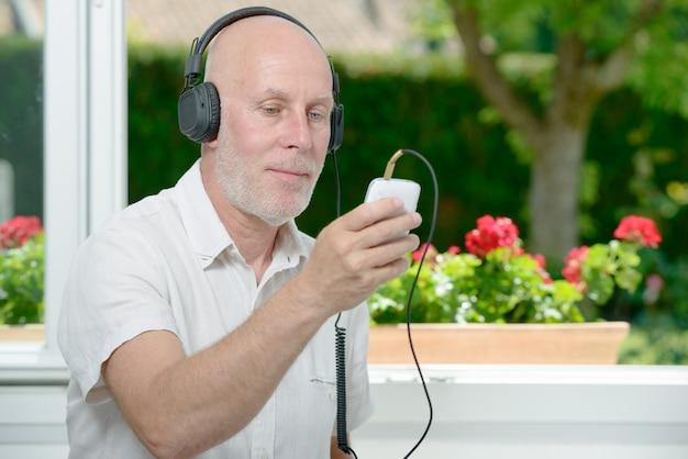 Rijpe mens die aan muziek met zijn telefoon luistert