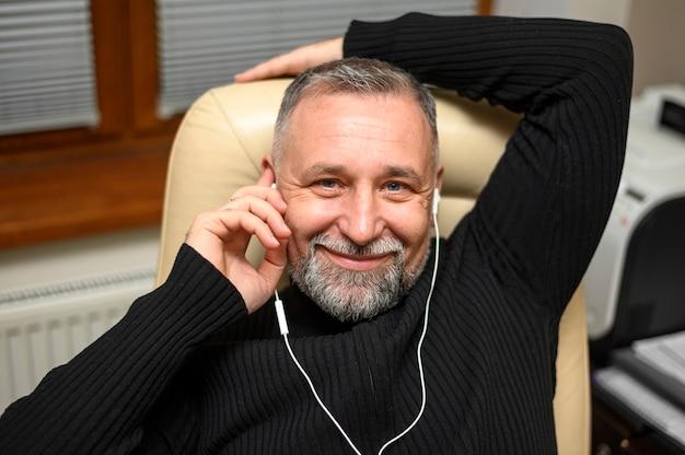 Rijpe mens die aan muziek thuis luistert