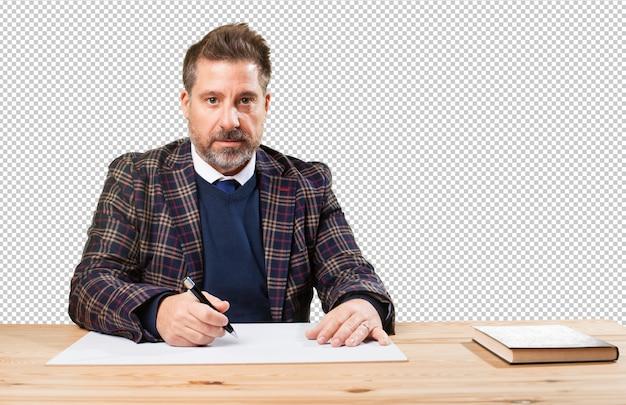 Rijpe mens die aan zijn desktop werkt