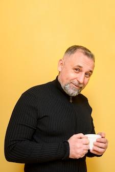 Rijpe mens die een kop van koffie naast een gele muur houdt