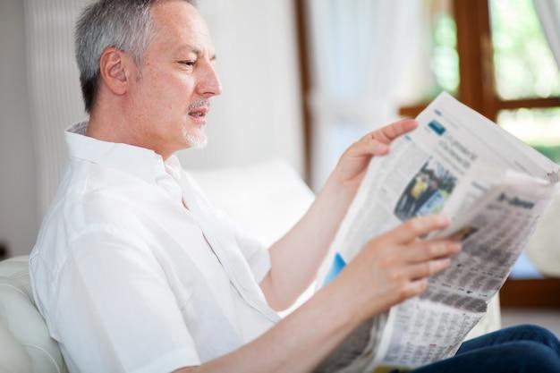 Rijpe mens die een krant in zijn woonkamer leest