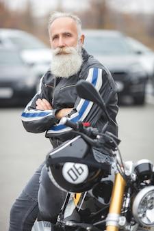 Rijpe mens die een motorfiets berijdt. oude man op motor. bebaarde man buitenshuis rijden.