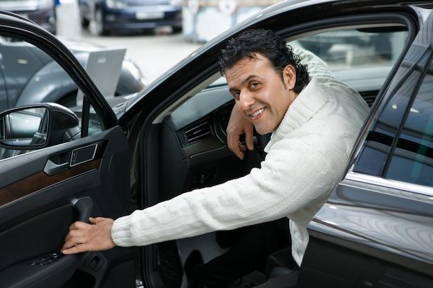 Rijpe mens die een nieuwe auto kiest bij de handel drijven salon