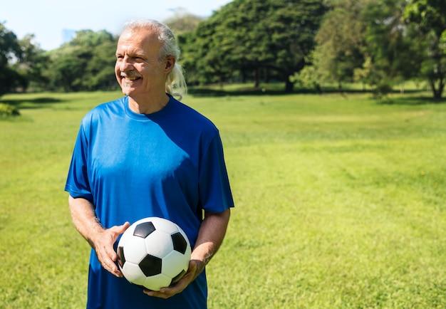 Rijpe mens die een voetbal houdt