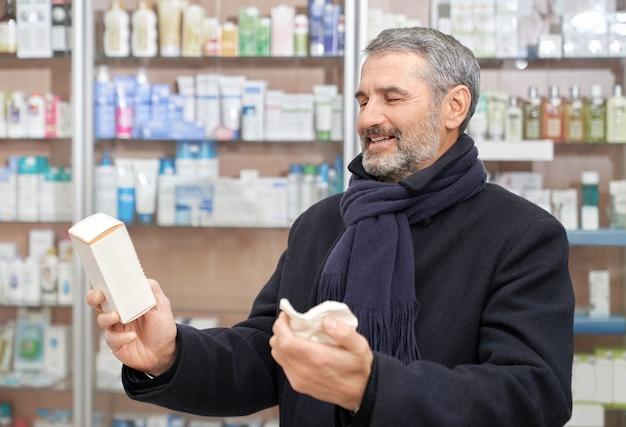 Rijpe mens die geneesmiddelen voor gezondheidszorg kiest.
