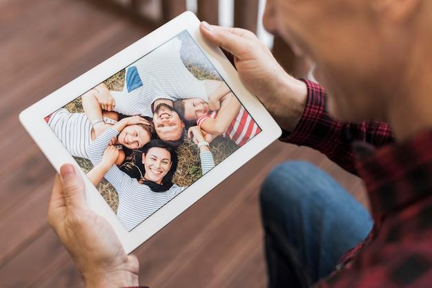 Rijpe mens die op foto's met zijn kinderen en kleinkinderen kijkt